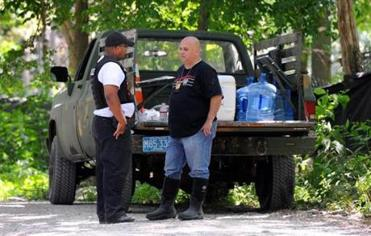 Westport 07/20/2016 : Police from Fall River, Dartmouth and Westport along with the Animal Rescue League and Westport animal control Dept., investigate a 70-acre property in Westport after many dead and injured animals were found there. (l-r) Westport officer Fernando Goncalves talks to Westport Detective Sgt. Tony Cestodio near the entrance. Photo by Debee Tlumacki for the Boston Globe (metro)